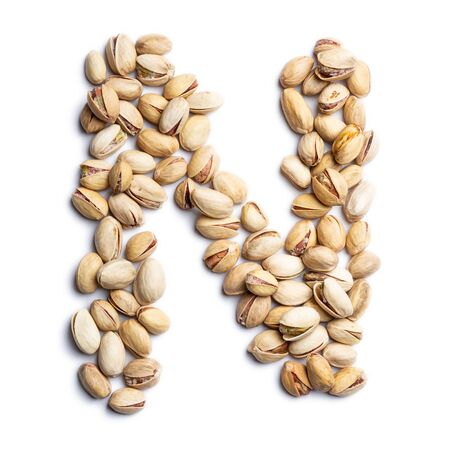 """The letter """"N"""" of the English alphabet from a unpeeled pistachios on a white isolated background. Unpeeled pistachios nuts pattern. healthy food concept. Letters for composing texts Reklamní fotografie"""