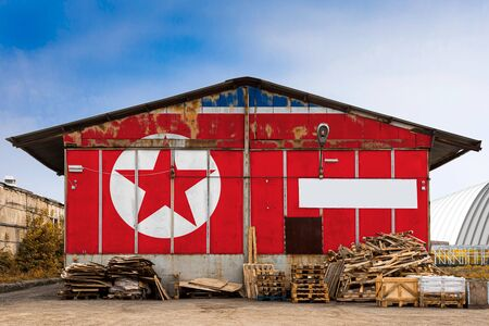 Close-up of the national flag of North Korea painted on the metal wall of a large warehouse the closed territory on a summer day. The concept of storage of goods, entry to a closed area, tourism