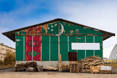 Close-up of the national flag of Turkmenistan painted on the metal wall of a large warehouse the closed territory on a summer day. The concept of storage of goods, entry to a closed area, tourism Stock fotó