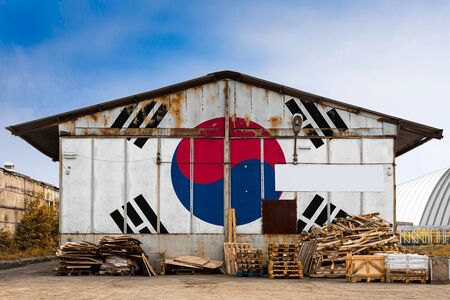 Close-up of the national flag of South Korea painted on the metal wall of a large warehouse the closed territory on a summer day. The concept of storage of goods, entry to a closed area, tourism