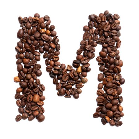 Letter M of the English alphabet of freshly roasted cocoa beans on a white isolated background. coffee pattern made from coffee beans. Font for coffein, the concept of vivacity and culture of coffee. Writing Letters