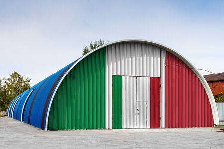 Close-up of the national flag of Italy painted on the metal wall of a large warehouse the closed territory against blue sky. The concept of storage of goods, entry to a closed area, logistics