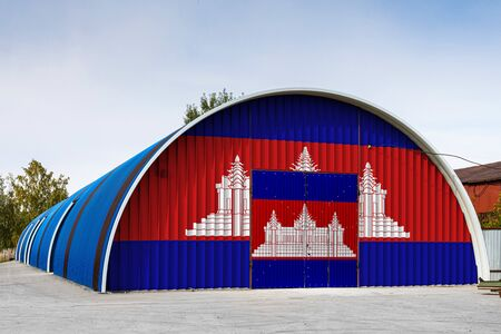 Close-up of the national flag of Cambodia painted on the metal wall of a large warehouse the closed territory against blue sky. The concept of storage of goods, entry to a closed area, logistics