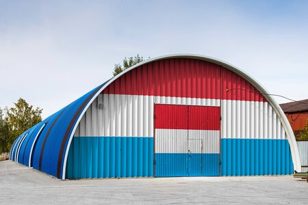 Close-up of the national flag of Luxembourg painted on the metal wall of a large warehouse the closed territory against blue sky. The concept of storage of goods, entry to a closed area, logistics