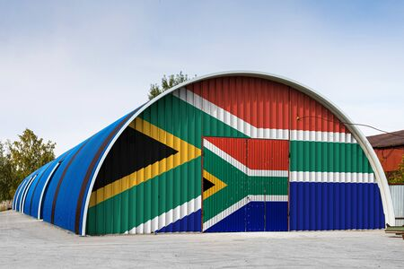 Close-up of the national flag of South African Republic painted on the metal wall of a large warehouse the closed territory against blue sky. The concept of storage of goods, entry to a closed area, logistics