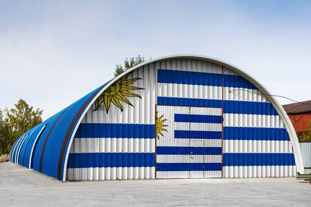 Close-up of the national flag of Uruguay painted on the metal wall of a large warehouse the closed territory against blue sky. The concept of storage of goods, entry to a closed area, logistics
