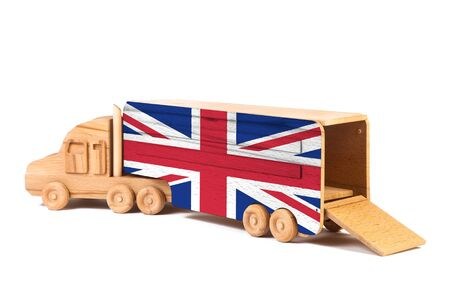 Close-up of a wooden toy truck with a painted national flag United Kingdom. The concept of export-import,transportation, national delivery of goods