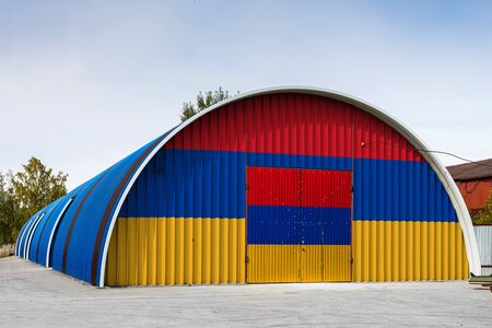 Close-up of the national flag of Armenia painted on the metal wall of a large warehouse the closed territory against blue sky. The concept of storage of goods, entry to a closed area, logistics Stok Fotoğraf