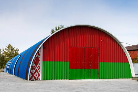 Close-up of the national flag of Belarus  painted on the metal wall of a large warehouse the closed territory against blue sky. The concept of storage of goods, entry to a closed area, logistics Stok Fotoğraf