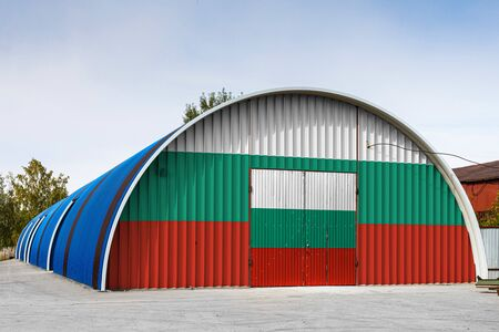 Close-up of the national flag of Bulgaria  painted on the metal wall of a large warehouse the closed territory against blue sky. The concept of storage of goods, entry to a closed area, logistics