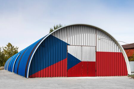 Close-up of the national flag of Czech painted on the metal wall of a large warehouse the closed territory against blue sky. The concept of storage of goods, entry to a closed area, logistics Stok Fotoğraf