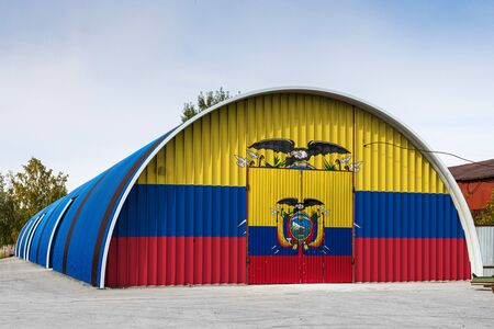 Close-up of the national flag of Ecuador  painted on the metal wall of a large warehouse the closed territory against blue sky. The concept of storage of goods, entry to a closed area, logistics