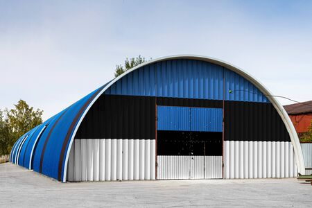 Close-up of the national flag of Estonia  painted on the metal wall of a large warehouse the closed territory against blue sky. The concept of storage of goods, entry to a closed area, logistics Stok Fotoğraf