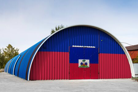 Close-up of the national flag of Haiti  painted on the metal wall of a large warehouse the closed territory against blue sky. The concept of storage of goods, entry to a closed area, logistics