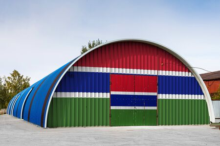 Close-up of the national flag of Gambia  painted on the metal wall of a large warehouse the closed territory against blue sky. The concept of storage of goods, entry to a closed area, logistics Stok Fotoğraf