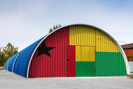 Close-up of the national flag of Guinea Bissau painted on the metal wall of a large warehouse the closed territory against blue sky. The concept of storage of goods, entry to a closed area, logistics