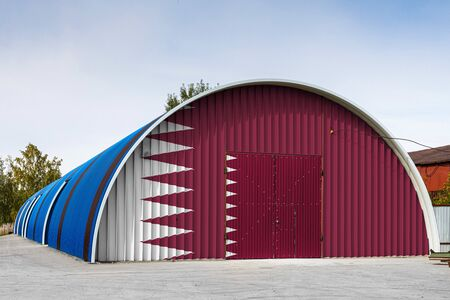 Close-up of the national flag of Qatar  painted on the metal wall of a large warehouse the closed territory against blue sky. The concept of storage of goods, entry to a closed area, logistics