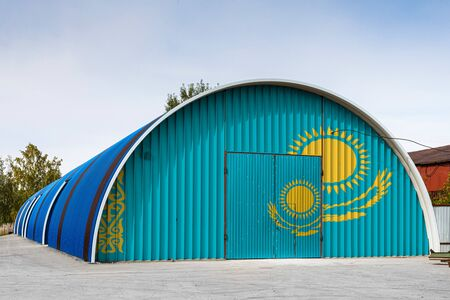 Close-up of the national flag of Kazakhstan painted on the metal wall of a large warehouse the closed territory against blue sky. The concept of storage of goods, entry to a closed area, logistics
