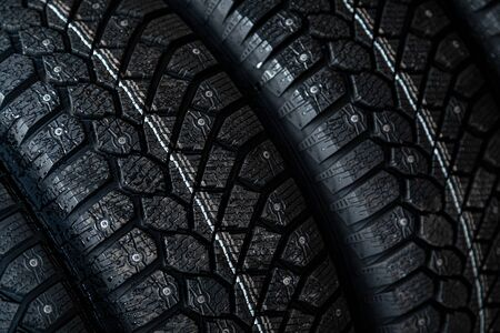 Close-up black new studded tires for winter driving in a car