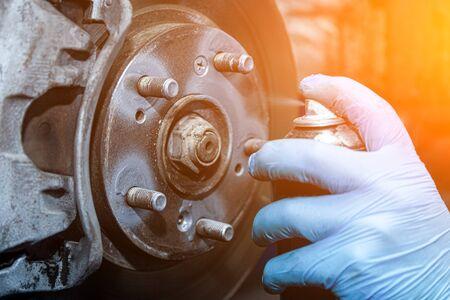 Close-up Workshop worker in protective gloves lubricates wheel studs, brake repair. Work at the tire workshop Stok Fotoğraf