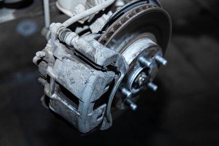 Close-up of a car hub, brake caliper, brake pads, brake disc, wheel bearing prepared for repair. Work at the tire workshop