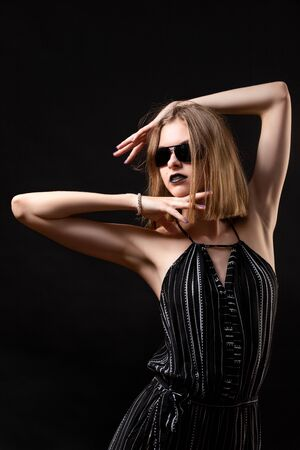 A young woman with black overalls and black glasses holds her hands near her head in the form of a frame and poses on a black isolated background.  Portrait of a beautiful woman in minimalistic fashion style. Stok Fotoğraf