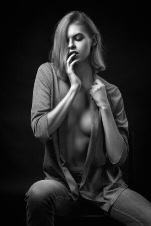 Sensual Young woman in a gray sweater and jeans sits on a chair and poses on a black isolated background. Fashion photography in black and white style.