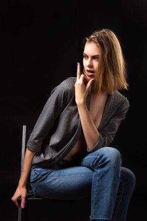 Sensual Young woman in a gray sweater and jeans sits on a chair and poses on a black isolated background. Portrait of a beautiful woman in minimalistic fashion style. Stok Fotoğraf