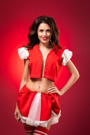 Mrs. Santa Claus New Year portrait of a young woman in a red suit smiling charmingly and posing against a red isolated background. Charming women for Christmas designs