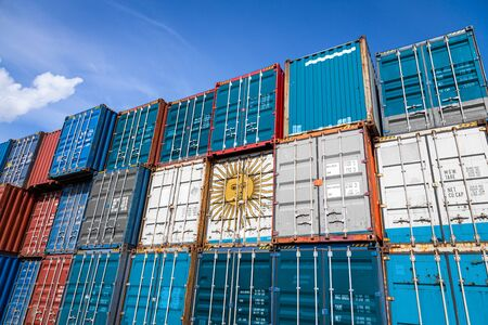 The national flag of Argentina on a large number of metal containers for storing goods stacked in rows on top of each other. Conception of storage of goods by importers, exporters Stock Photo