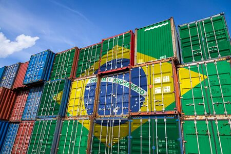 The national flag of Brazil on a large number of metal containers for storing goods stacked in rows on top of each other. Conception of storage of goods by importers, exporters