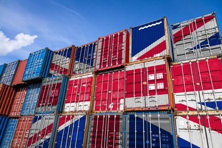 The national flag of United Kingdom on a large number of metal containers for storing goods stacked in rows on top of each other. Conception of storage of goods by importers, exporters