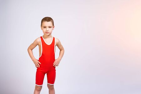 Portrait of a little cheerful boy in a red wrestling tights holds his hands on his sides, looks confidently at the camera and poses on a white isolated background. The concept of a little fighter athlete