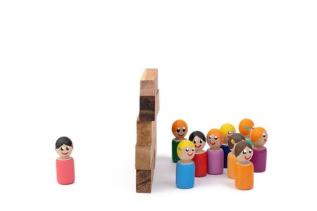 A team of wooden toys and a lonely woman are separated by a high wall. The image of the separation of families by dictatorial methods. The concept of lonely life.