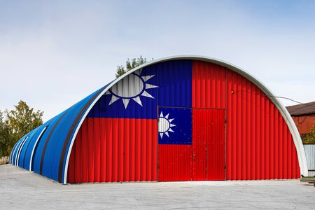 Close-up of the national flag of Taiwan  painted on the metal wall of a large warehouse the closed territory against blue sky. The concept of storage of goods, entry to a closed area, logistics Reklamní fotografie