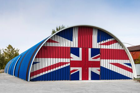 Close-up of the national flag of United Kingdom painted on the metal wall of a large warehouse the closed territory against blue sky. The concept of storage of goods, entry to a closed area, logistics