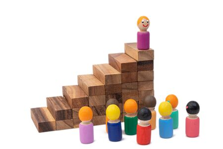 A wooden toy woman stands on a high pyramid stairs and looks out at a large number of people who obey her. The concept of the ruling woman and the dictator. Images of the population and the president