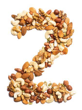 """Arabische Zahl """"2"""" aus geschälter Haselnuss auf weißem, isoliertem Hintergrund. Lebensmittelmuster aus Nüssen. helle Ziffer für Design. Standard-Bild"""