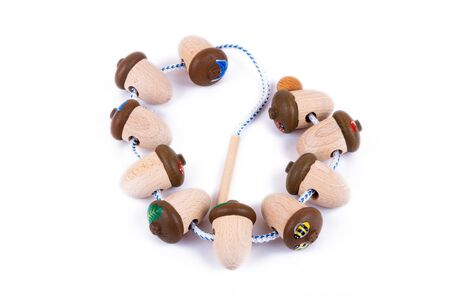 A close-up of children's toys made of natural wood in the form of acorns with shells, painted with different patterns - butterflies, flowers, bees. Eco-friendly toy for parents and children