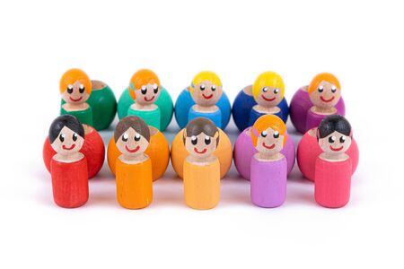 A close-up of a childrens toy made of natural wood in the form of little people of different colors with a smile is standing in an even row on a white isolated background. Teamwork concept. Eco-friendly toy for parents and children 版權商用圖片