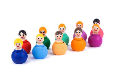 Close-up of a childrens toy made of natural wood in the form of little people of different colors with a smile on a white isolated background. A group of small toy men and women smiling and looking at the camera. Eco-friendly toy for parents and children