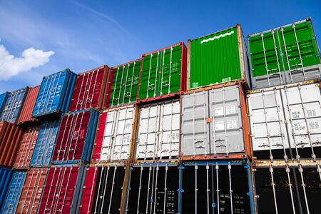 The national flag of United Arab Emirates on a large number of metal containers for storing goods stacked in rows on top of each other. Conception of storage of goods by importers, exporters