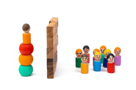 Wooden eco-toys, separated by a huge wall: on the one hand, one man is trying to get over, and on the other, a large crowd is waiting for his return. The concept of dividing people by the big wall Zdjęcie Seryjne