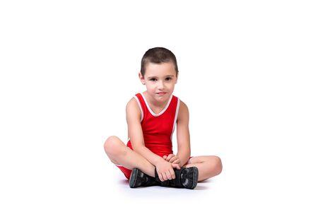Sportieve vrolijke jongen in een blauwe worstelpanty is klaar om deel te nemen aan sportoefeningen, zit op de vloer op een witte geïsoleerde achtergrond Stockfoto