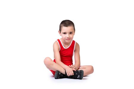 Sporty cheerful boy in a blue wrestling tights is ready to engage in sports exercises, is sitting on the floor on a white isolated background Stock fotó