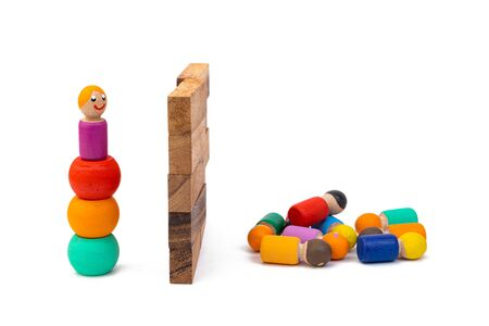 Wooden eco-toys, separated by a huge wall: on the one hand, one man is trying to get over, and on the other, a large crowd is no longer waiting. The concept of dividing people by the big wall Zdjęcie Seryjne - 135389226