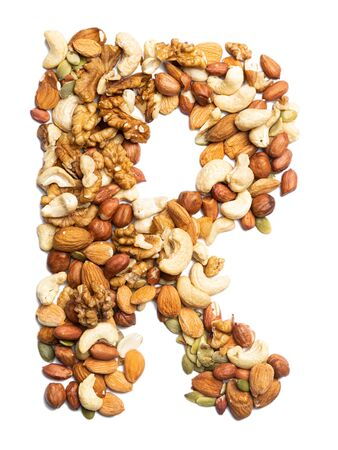Letter R of the English alphabet from a mixture of hazelnuts, almonds, walnuts, peanuts, cashews, pumpkin seeds on a white isolated background. Food pattern made from nuts. Bright alphabet for shops. Reklamní fotografie