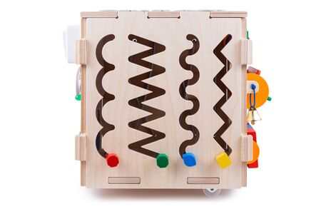 Ð¡lose-up of a labyrinth with multi-colored puzzles on a wooden busy board- educational toy for children, babies on a white isolated background. A toy for entertaining children and resting parents