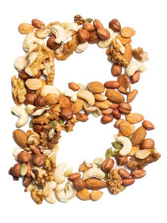 Buchstabe B des englischen Alphabets aus einer Mischung aus Haselnüssen, Mandeln, Walnüssen, Erdnüssen, Cashewnüssen, Kürbiskernen auf weißem, isoliertem Hintergrund. Lebensmittelmuster aus Nüssen. Helles Alphabet für Geschäfte.