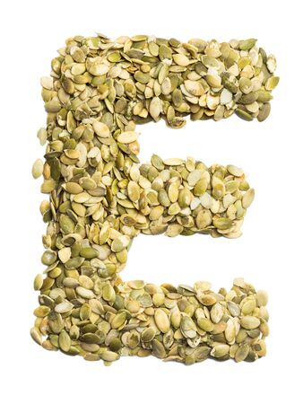 Letter E of the English alphabet from pumpkin seeds on a white isolated background. Food pattern made from seeds. Bright alphabet for shops. Zdjęcie Seryjne